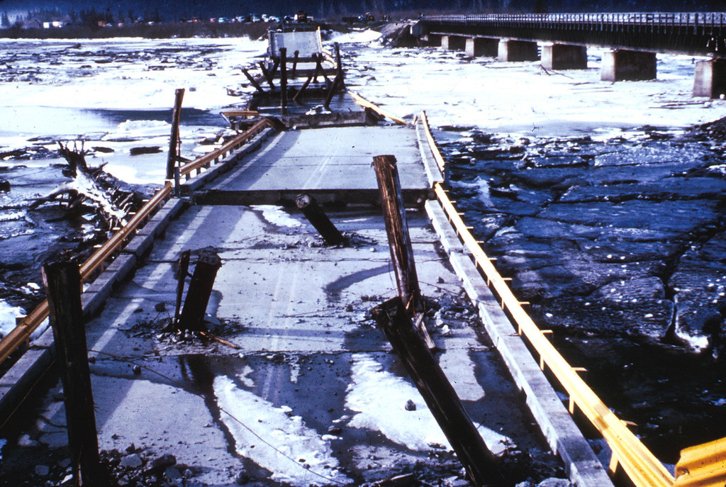 . Alaska Earthquake March 27, 1964. Twentymile River Bridge near Turnagain Arm on Cook Inlet. The bridge fell into the river, and some of the wood piles were driven through the reinforced concrete deck. The adjacent steel railroad bridge survived with only minor damage. Both bridges were founded on thick deposits of soft alluvium and tidal flat mud and were subjected to severe seismic vibration. U.S. Geological Survey photo