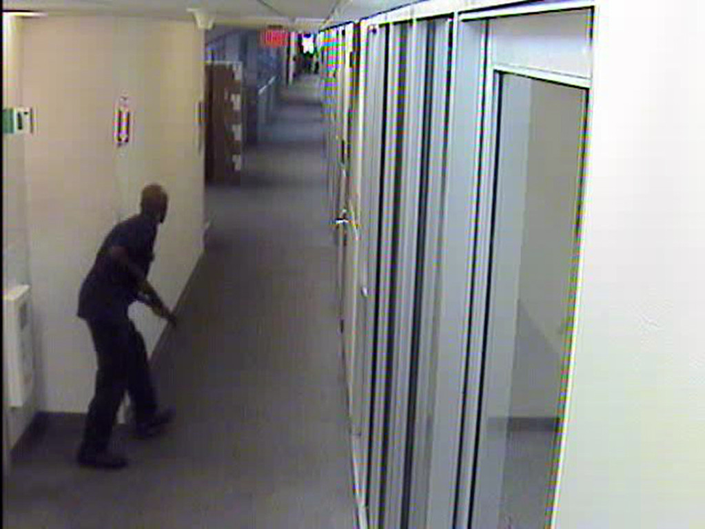 . This image from video provided by the FBI, shows Aaron Alexis moves through the hallways of Building #197 at the Washington Navy Yard on Monday, Sept. 16, 2013, in Washington, carrying a Remington 870 shotgun.  (AP Photo/FBI)
