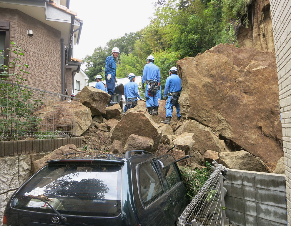 . Fire fighters stand on rocks fallen from a cliff over a garage and a road in a residential area in Kamakura, southwest of Tokyo, after a powerful typhoon hit Japan\'s metropolitan area Wednesday morning, Oct. 16, 2013.  (AP Photo/Kyodo News)