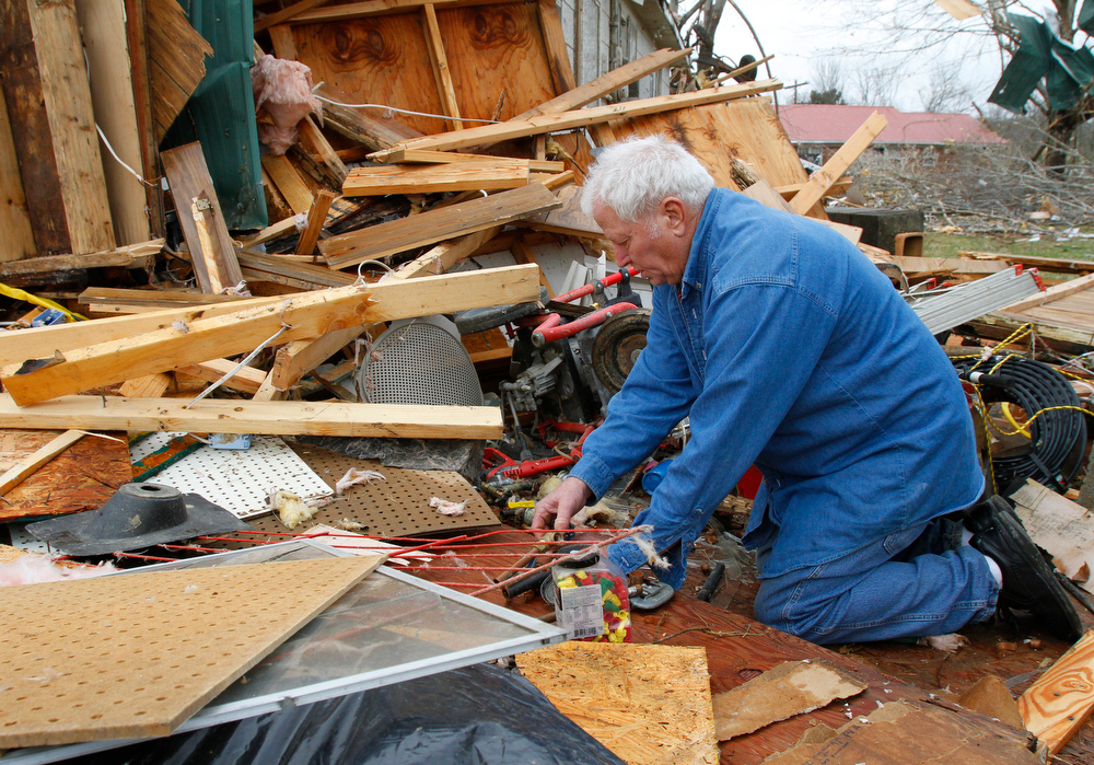 Description of . Ronnie Shanes searches through debris of his brother's home after a storm ripped through Coble, Tenn. early Wednesday, Jan. 30, 2013. A large storm system packing high winds, hail and at least one tornado tore across a wide swath of the South and Midwest on Wednesday, killing one person, blacking out power to thousands and damaging homes. (AP Photo/Butch Dill)