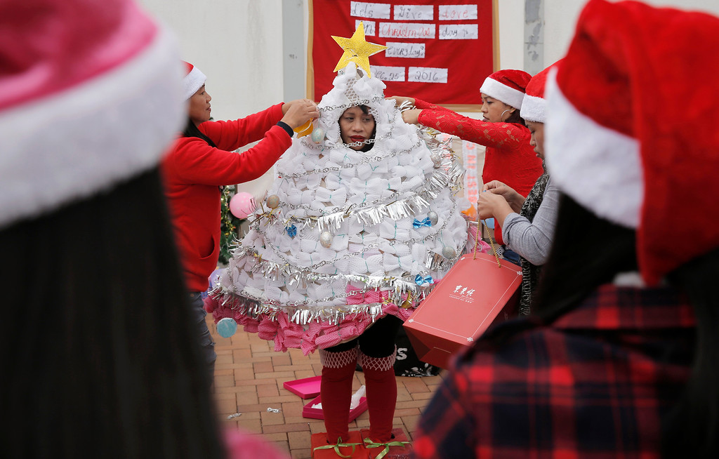 . A Filipino domestic helper is helped by her friends to dress up as a Christmas tree made with recycled materials and leaves as they hold a costume contest to celebrate the festival season in Hong Kong, Sunday, Dec. 25, 2016. (AP Photo/Kin Cheung)