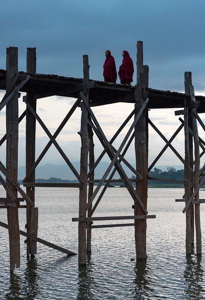 Buddhist monks walk the U Bein Bridge across the Taungthaman Lake in Amarapura near Mandalay, Burma (Myanmar)