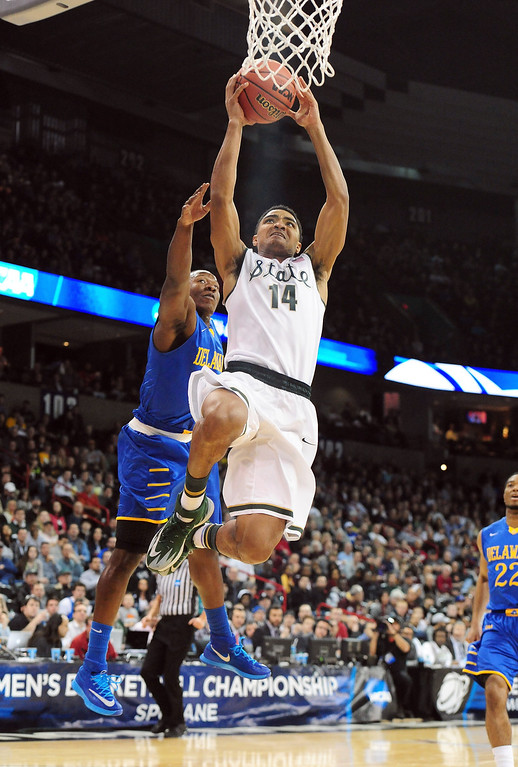. Gary Harris #14 of the Michigan State Spartans goes up for a shot on Devon Saddler #10 of the Delaware Fightin Blue Hens during the second round of the 2014 NCAA Men\'s Basketball Tournament at Spokane Veterans Memorial Arena on March 20, 2014 in Spokane, Washington.  (Photo by Steve Dykes/Getty Images)