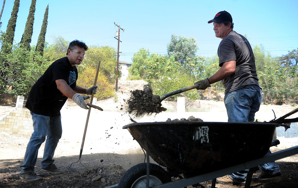 . Volunteer\'s Cesar Hakim, left, with Gus Berenger shovel dirt and debris into a wheel barrel as Pomona Valley Habitat for Humanity and Verizon employees work to clear an area where a home will be built for a veteran on Wednesday, Aug. 14, 2013 in Walnut, Calif.   (Keith Birmingham/Pasadena Star-News)
