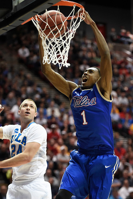 . Tulsa forward Rashad Smith, right, dunks the basket as UCLA forward Travis Wear, left, looks on during the first half of a second-round game in the NCAA college basketball tournament Friday, March 21, 2014, in San Diego. (AP Photo/Denis Poroy)