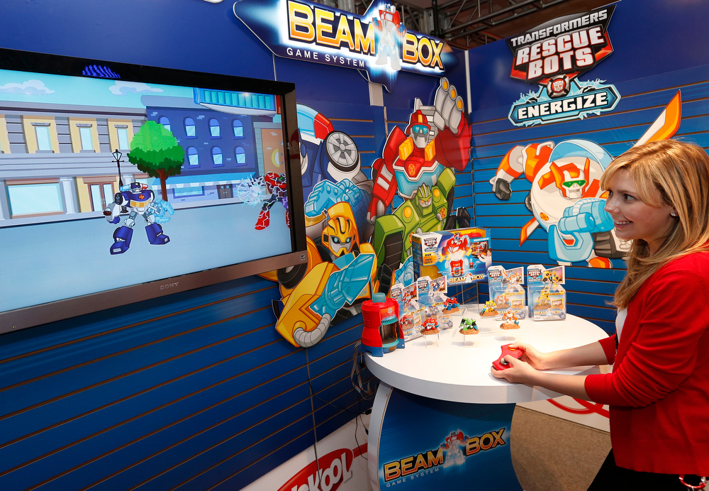 Description of . Demonstrator Sharon Juchniewicz plays the TRANSFORMERS RESCUE BOTS BEAM BOX game in Hasbroís showroom at the American International Toy Fair, Friday, Feb. 8, 2013, in New York.  Interactive missions packed with lights, sounds and signature TRANSFORMERS RECUE BOTS character voices transport kids into an adventurous world of gameplay and mini-missions this fall. (Photo by Jason DeCrow/Invision for Hasbro/AP Images)