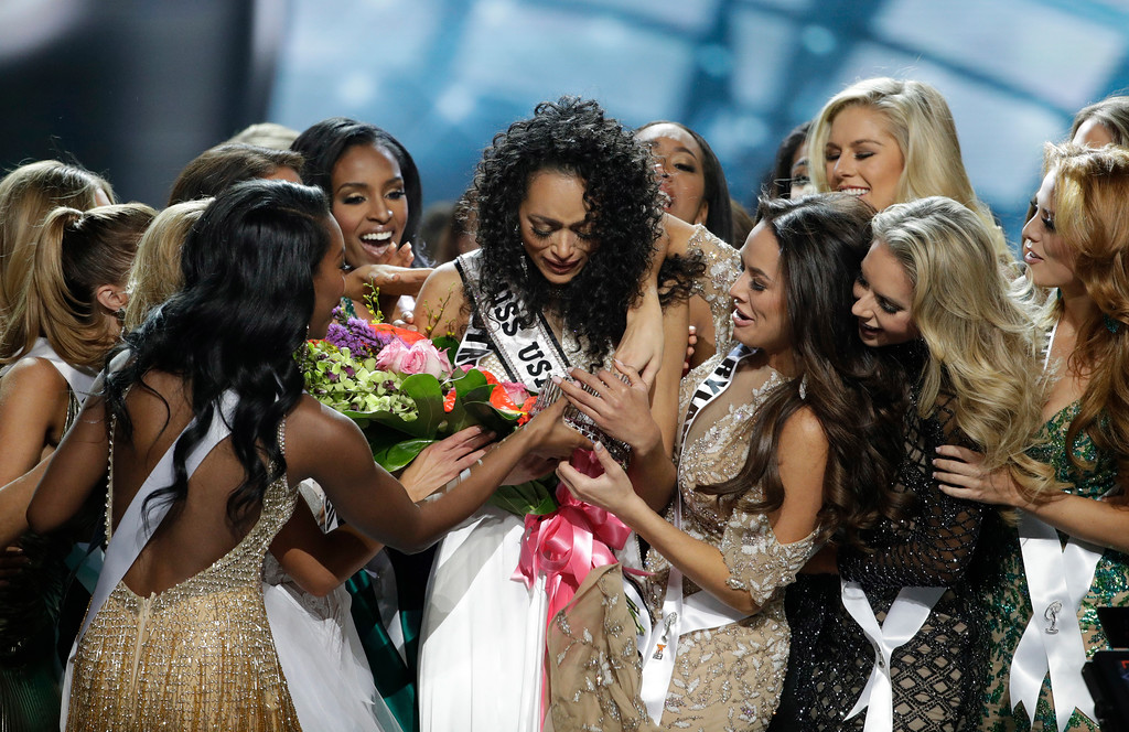 . Miss District of Columbia USA Kara McCullough, center, reacts with fellow contestants after she was crowned the new Miss USA during the Miss USA contest Sunday, May 14, 2017, in Las Vegas. (AP Photo/John Locher)