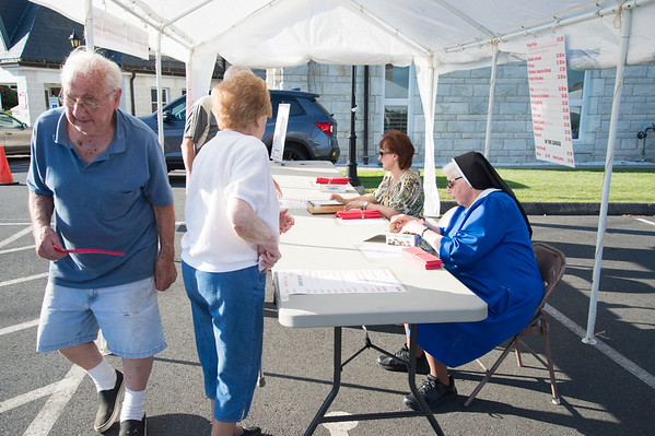 06/28/19 Wesley Bunnell | Staff The Sacred Heart Partish Festival, Odpus, opened Friday June 28, 2019 and will continue thru Saturday. A visitor leaves the table selling food tickets as Mother Jennifer helps.