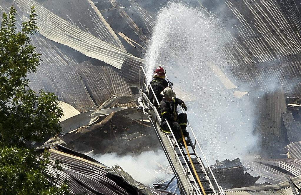 . Argentinian firefighters try to extinguish a fire on a warehouse located in southern Buenos Aires, Argentina, 05 February 2014.  EPA/DAVID FERNANDEZ