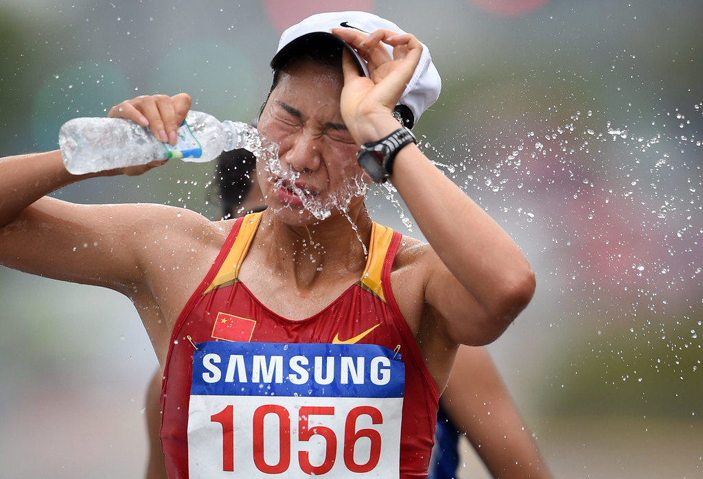 . Nie Jingjing of China splashes water on her face as she competes in the final of the women\'s 20km race walk athletics event during the 17th Asian Games on the Race Walking Course in Incheon on September 28, 2014. ED JONES/AFP/Getty Images