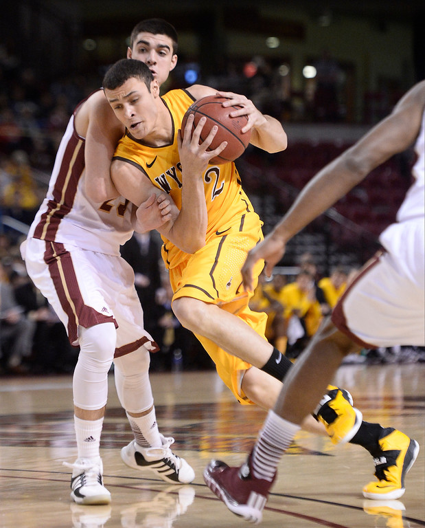 . Wyoming Cowboys forward Larry Nance Jr. (22) drives on Denver Pioneers guard Brett Olson (23) during the first half December 15, 2013 Magness Arena. (Photo by John Leyba/The Denver Post)