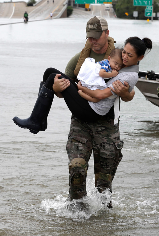 . Houston Police SWAT officer Daryl Hudeck carries Catherine Pham and her 13-month-old son Aiden after rescuing them from their home surrounded by floodwaters from Tropical Storm Harvey Sunday, Aug. 27, 2017, in Houston. (AP Photo/David J. Phillip)