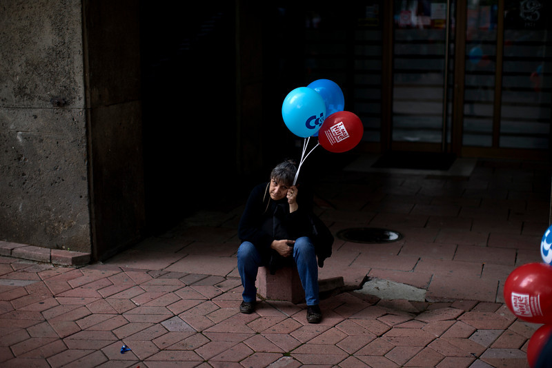 . A woman sits on the fringes of a May Day protest in Belgrade, Serbia, Thursday, May 1, 2014. Various labor groups staged a protest in Belgrade in order to voice their concern over the expected austerity measures announced by Serbia\'s new government. (AP Photo/Marko Drobnjakovic)