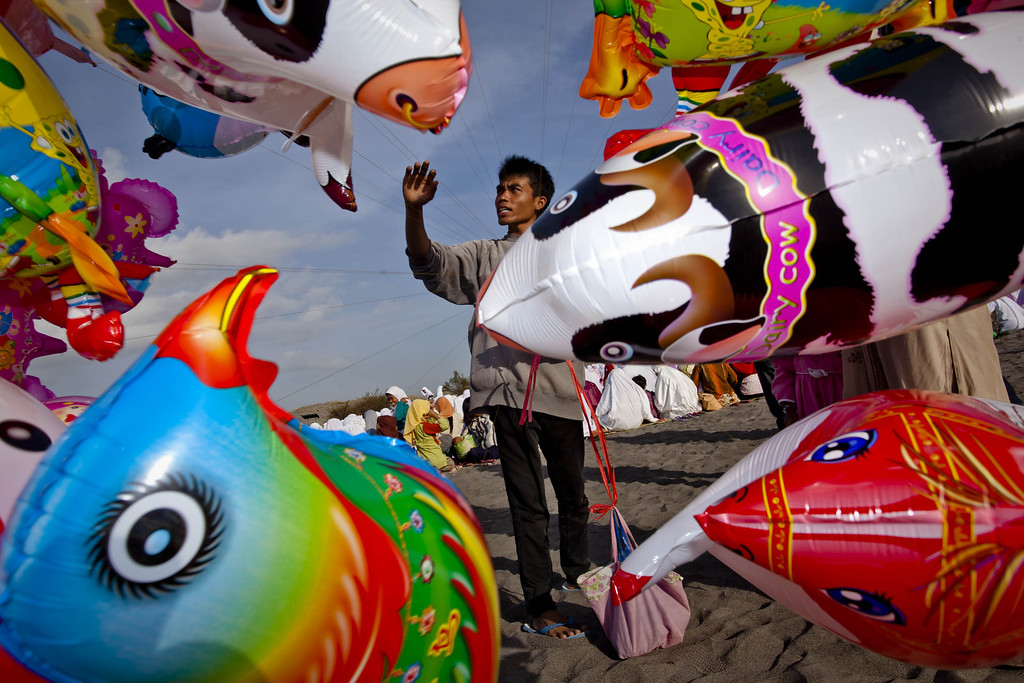 . A man sells balloons as Indonesian muslims attend Eid Al-Adha prayer at Parangkusumo beach on October 15, 2013 in Yogyakarta, Indonesia.   (Photo by Ulet Ifansasti/Getty Images)