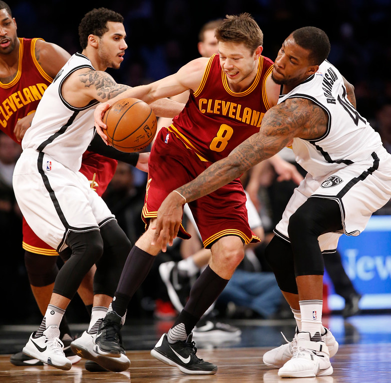 . Brooklyn Nets forward Thomas Robinson (41) defends Cleveland Cavaliers guard Matthew Dellavedova (8) in the second half of an NBA basketball game, Wednesday, Jan. 20, 2016, in New York. The Cavaliers defeated the Nets 91-78. Brooklyn Nets guard Shane Larkin (0) gets in on the play, defending, at left. (AP Photo/Kathy Willens)