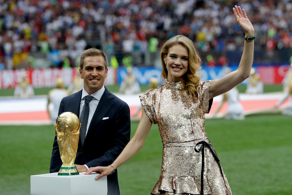 . Former German soccer team captain Philipp Lahm and Russian model Natalia Vodianova display the trophy before the final match between France and Croatia at the 2018 soccer World Cup in the Luzhniki Stadium in Moscow, Russia, Sunday, July 15, 2018. (AP Photo/Matthias Schrader)