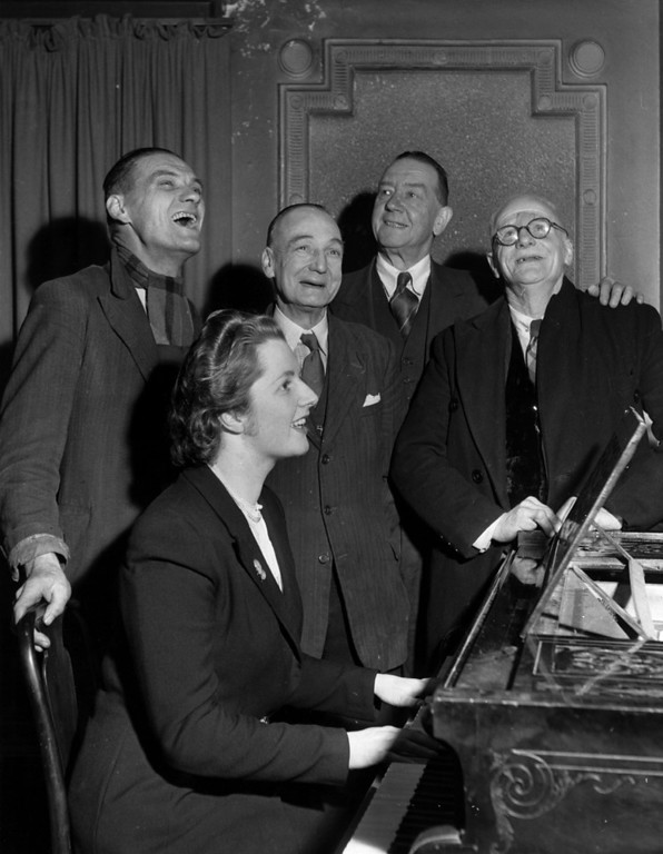 . Conservative candidate Margaret Roberts accompanies four voters on the piano in a sing-song after a brief political argument in the bar of The Bull Inn, Dartford.  (Margaret Roberts married Denis Thatcher and went on to become Prime Minister.)  (Photo by Keystone/Getty Images)