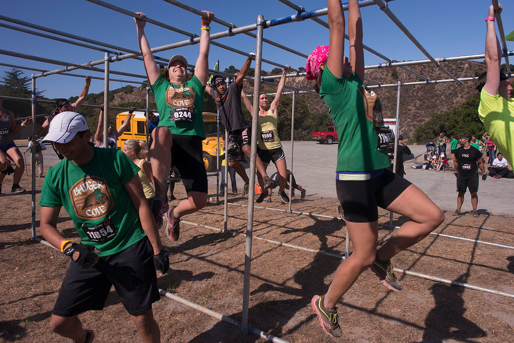 . The Bauger Cove team attacks the monkey bars, Saturday August 10th, 2013, during the first annual Monterey Spartan Race. (Matthew Hintz/Montery County Herald)