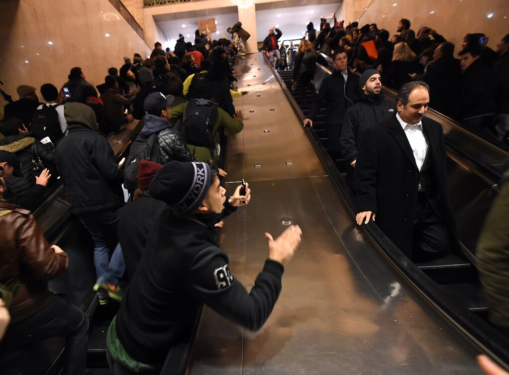 . Protestors shout in Grand Central Station during a protest on December 3, 2014 after a grand jury decided not to charge a white police officer in the choking death of Eric Garner, a black man, days after a similar decision sparked renewed unrest in Missouri. Eric Garner died after being placed in a chokehold by New York police Officer Daniel Pantaleo while being arrested on suspicion of selling untaxed cigarettes in Staten Island. AFP PHOTO / Timothy  A. CLARY/AFP/Getty Images