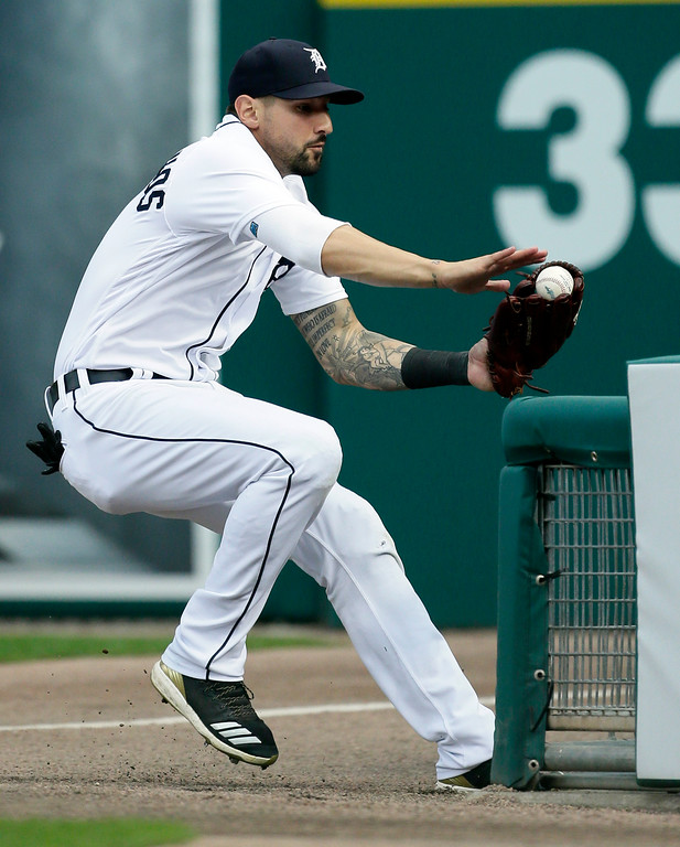 . Detroit Tigers right fielder Nicholas Castellanos tries to avoid the fence in foul territory after catching a foul ball for the out on Cleveland Indians\' Brandon Guyer during the sixth inning of a baseball game Saturday, July 28, 2018, in Detroit. (AP Photo/Duane Burleson)