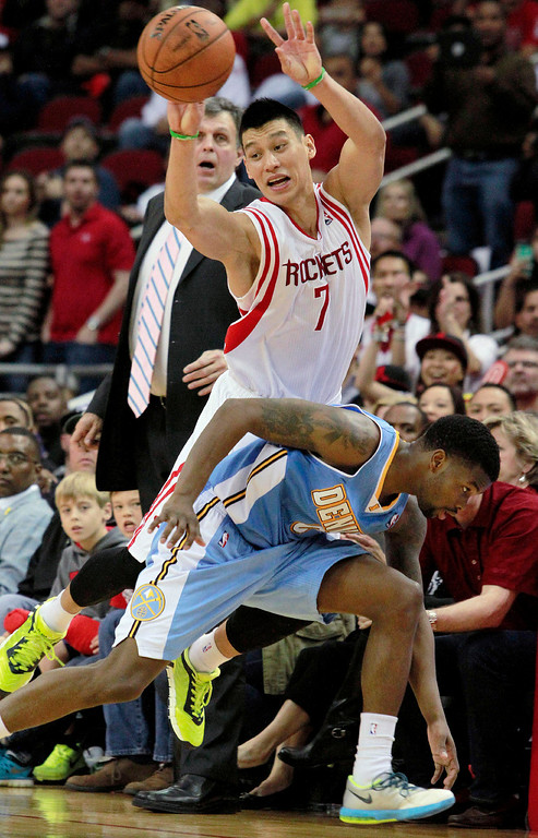 . Houston Rockets guard Jeremy Lin looks to pass after stealing the ball from Denver Nuggets guard Aaron Brooks during an NBA basketball game in Houston on Sunday, April 6, 2014.  The Rockets won the game 130-125 in overtime. (AP Photo/Richard Carson)
