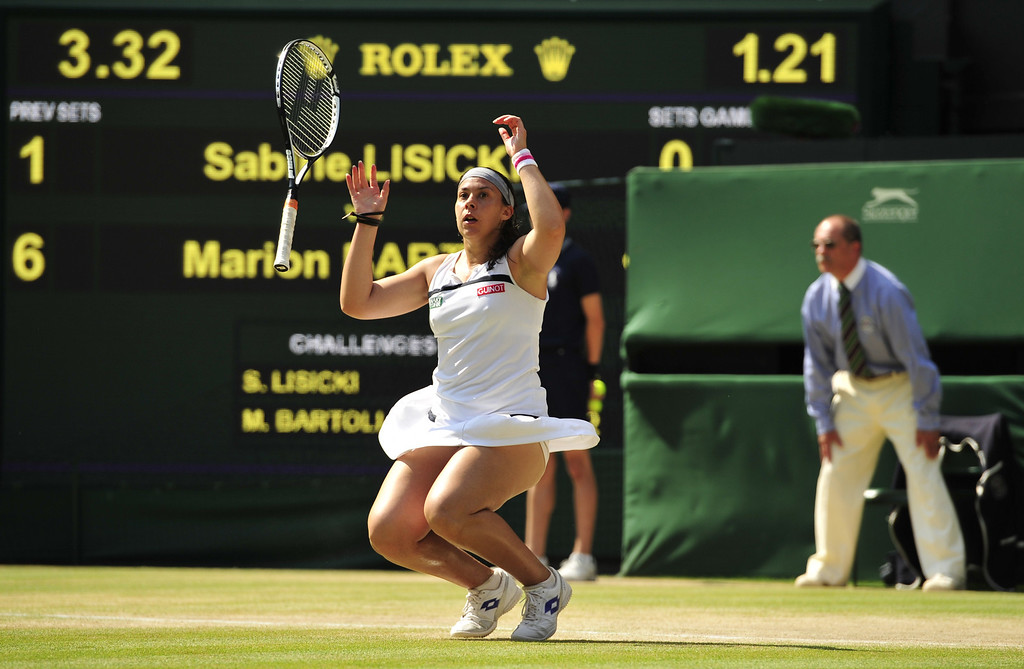 . France\'s Marion Bartoli drops her racquet and falls to her knees as she beats Germany\'s Sabine Lisicki in their women\'s singles final match on day twelve of the 2013 Wimbledon Championships tennis tournament at the All England Club in Wimbledon, southwest London, on July 6, 2013.  GLYN KIRK/AFP/Getty Images