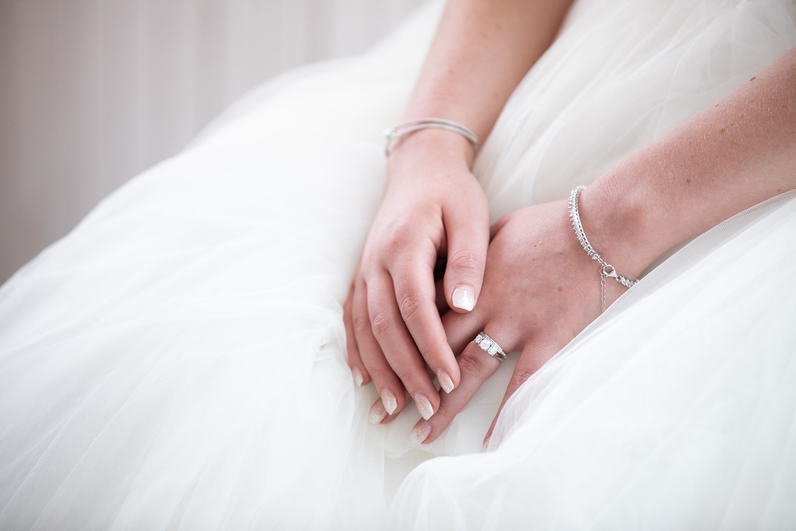 close up photo of a brides hand as she crosses them on her lap showing her simple bracelets and wedding ring