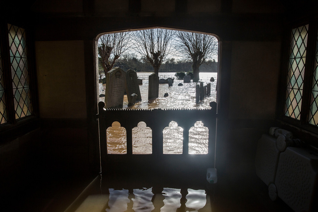 . Gravestones surrounded by floodwater in the grounds of St Deny\'s Church on February 13, 2014 in Severn Stoke, Worcestershire, England. The Environment Agency has issued flood warnings for dozens of areas along the River Severn. (Photo by Rob Stothard/Getty Images)