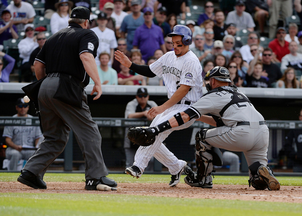 . Colorado Rockies third baseman, Nolan Arenado, crosses home safely against Chicago White Sox catcher, Tyler Flowers, in the 8th inning at Coors Field Wednesday afternoon, April 09, 2014. Arenado and teammate Drew Stubbs scored thanks to an RBI double hit by DJ LeMahieu. The Rockies went on to win 10-4. (Photo By Andy Cross / The Denver Post)