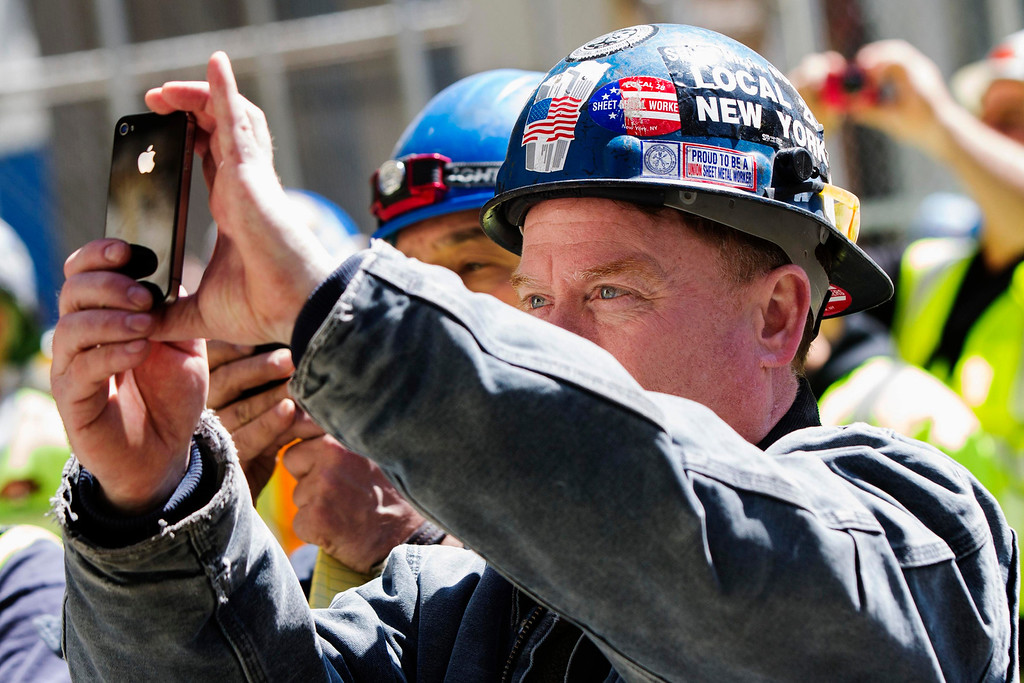 . Ground Zero workers photograph with their phones as the final piece of One World Trade Center\'s spire is lifted to the top of the building in New York, May 2, 2013. REUTERS/Lucas Jackson