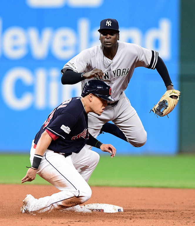 . New York Yankees\' Didi Gregorius, top, watches his throw to first after forcing out Cleveland Indians\' Giovanny Urshela at second base in the fifth inning of Game 5 of a baseball American League Division Series, Wednesday, Oct. 11, 2017, in Cleveland. Francisco Lindor was out at first base for the double play. (AP Photo/David Dermer)