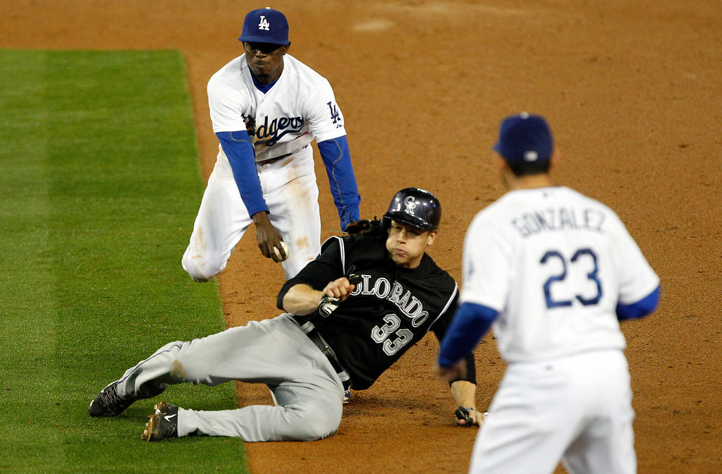. Los Angeles Dodgers second baseman Dee Gordon, top left, tags out Colorado Rockiesí Justin Morneau (33), then completes the ground ball double play by throwing to Dodgers first baseman Adrian Gonzalez (23) in time to get Rockies\' Wilin Rosario (not pictured) at first in the eleventh inning of a baseball game on Friday, April 25, 2014, in Los Angeles. Rockies won 5-4 in eleven innings. (AP Photo/Alex Gallardo)