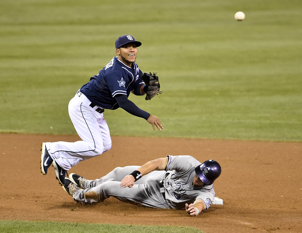 . SAN DIEGO, CA - SEPTEMBER 23:  Alexi Amarista #5 of the San Diego Padres throws over DJ LeMahieu #9 of the Colorado Rockies as he turns a double play during the fourth inning of a baseball game at Petco Park September, 23, 2014 in San Diego, California.  (Photo by Denis Poroy/Getty Images)