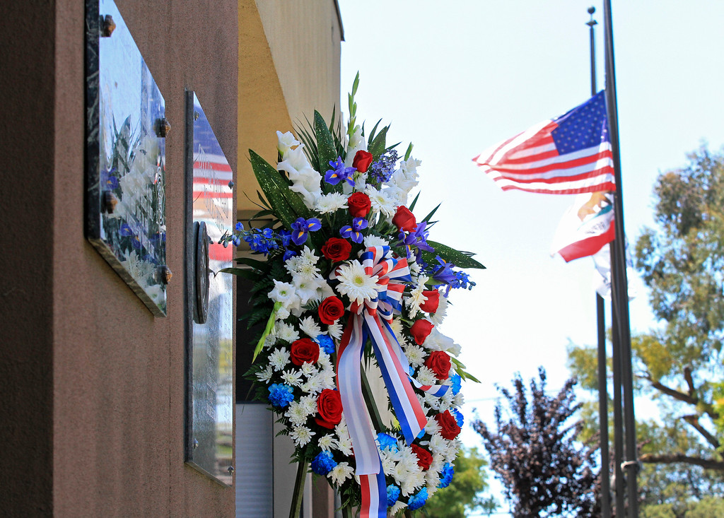 . Flowers and cards of condolences from the community sit outside the Hayward Police Department where flags are at half staff in Hayward, Calif., on Wednesday, July 22, 2015. Sgt. Scott Lunger  was shot and killed early Wednesday morning during a routine traffic stop. (Laura A. Oda/Bay Area News Group)