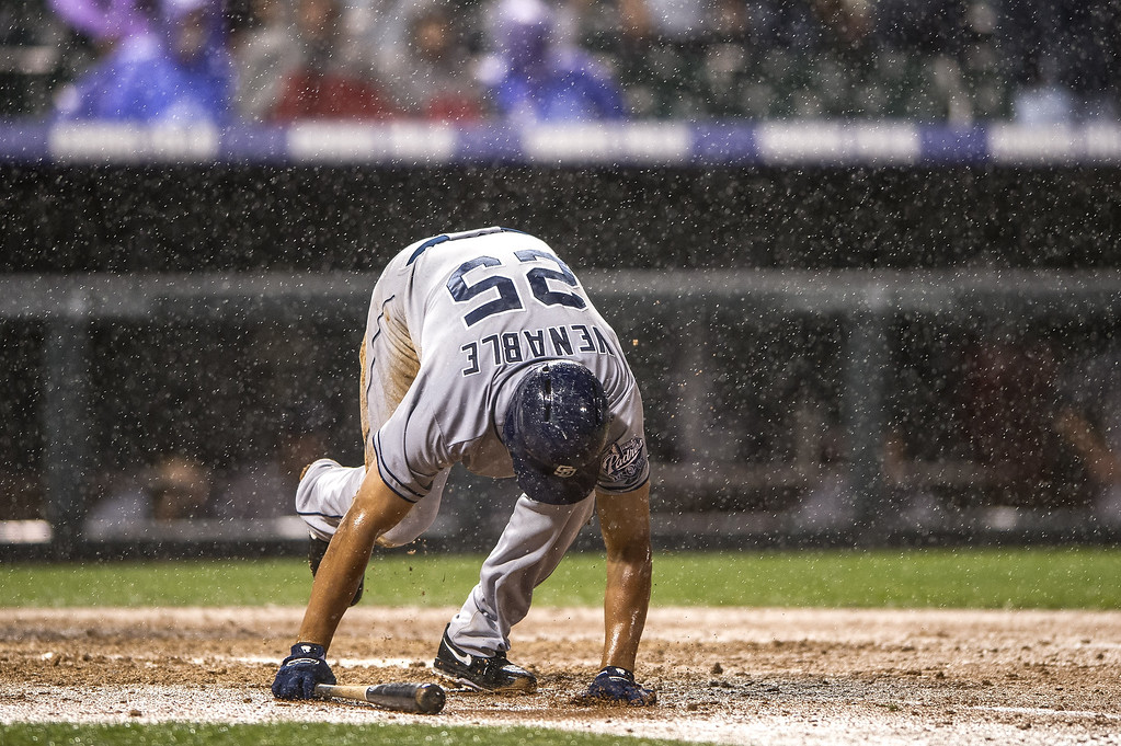 . Will Venable #25 of the San Diego Padres slips out of the batter\'s box as rain falls during a game against the Colorado Rockies at Coors Field on August 12, 2013 in Denver, Colorado. A rain delay was called in the eighth inning with the Rockies leading 8-1.  (Photo by Dustin Bradford/Getty Images)