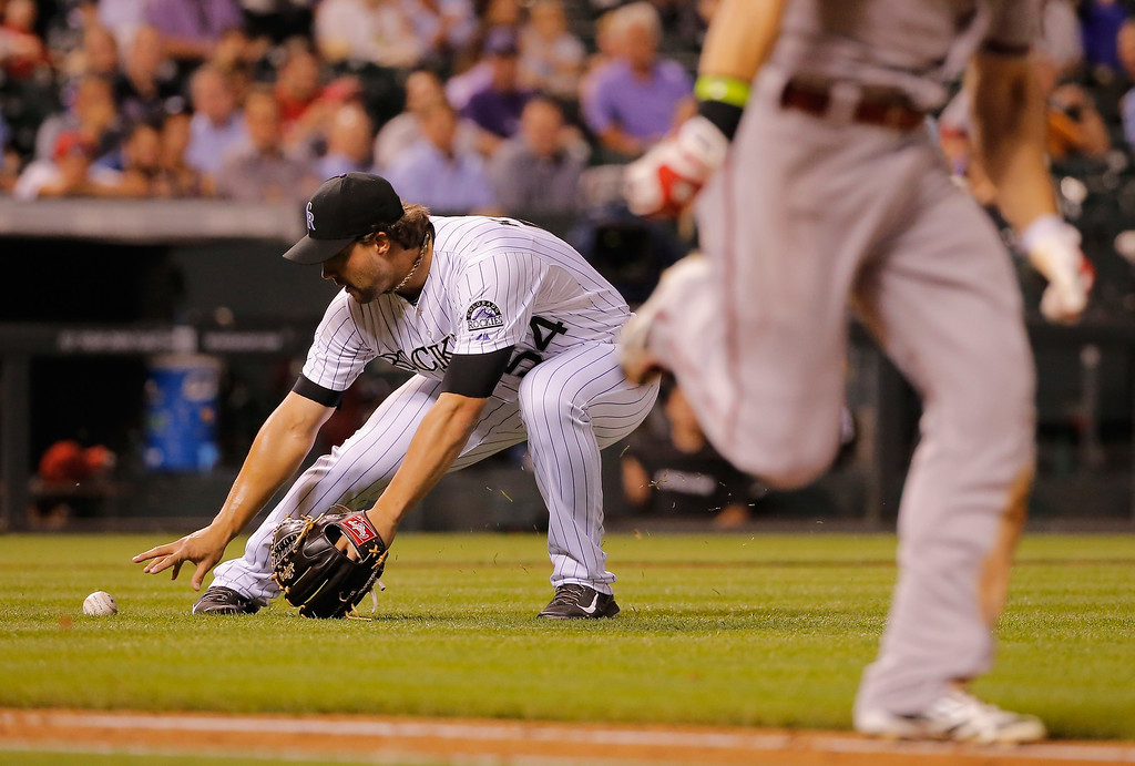 . DENVER, CO - SEPTEMBER 18:  Relief pitcher Tommy Kahnle #54 of the Colorado Rockies fields a bunt single by Ender Inciarte #5 of the Arizona Diamondbacks in the sixth inning at Coors Field on September 18, 2014 in Denver, Colorado.  (Photo by Doug Pensinger/Getty Images)