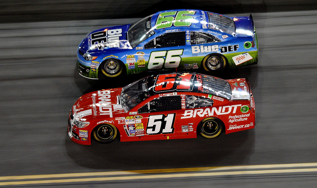 . Justin Allgaier, driver of the #51 Brandt Professional Agriculture Chevrolet, races Michael Waltrip, driver of the #66 BlueDEF/AAA Toyota, during the NASCAR Sprint Cup Series Budweiser Duel 2 at Daytona International Speedway on February 20, 2014 in Daytona Beach, Florida.  (Photo by Jared C. Tilton/Getty Images)