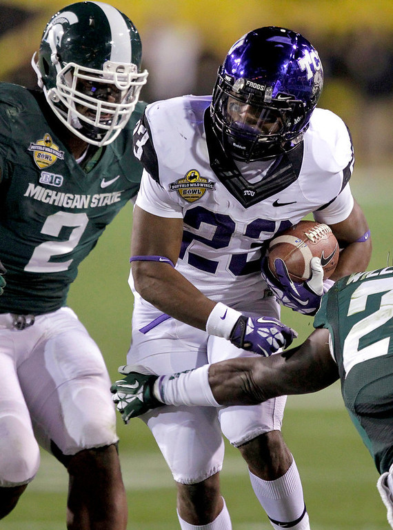 . TCU running back B.J. Catalon (23) gains yards as Michigan State Spartans defensive end William Gholston (2) defends during the first half of the Buffalo Wild Wings Bowl NCAA college football game, Saturday, Dec. 29, 2012, in Tempe, Ariz. (AP Photo/Matt York)
