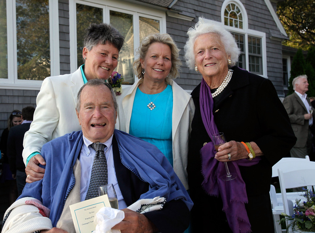 . In this Sept. 21, 2013 photo, former President George H.W. Bush, front left, former first lady Barbara Bush, right, pose for photos after wedding of longtime friends Helen Thorgalsen, center, and Bonnie Clement, in Kennebunkport, Maine. Bush was an official witness at the same-sex wedding, his spokesman said Wednesday, Sept. 25, 2013. (AP Photo/Susan Biddle)