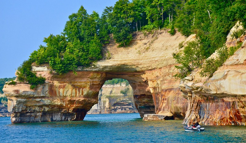 a boat in the water heading to an arch in a sandstone cliff