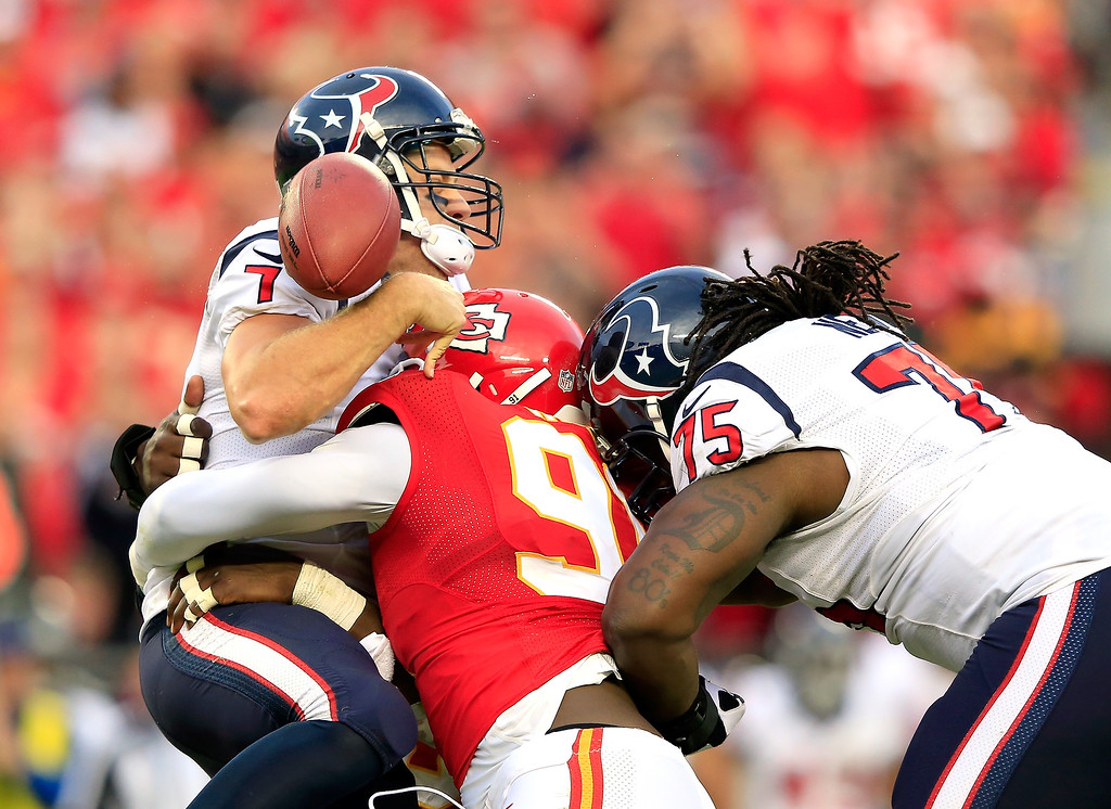 . Quarterback Case Keenum #7 of the Houston Texans loses the ball as he is sacked by outside linebacker Tamba Hali #91 of the Kansas City Chiefs as tackle Derek Newton #75 tries to block late in the 2nd half of the game at Arrowhead Stadium on October 20, 2013 in Kansas City, Missouri.  (Photo by Jamie Squire/Getty Images)