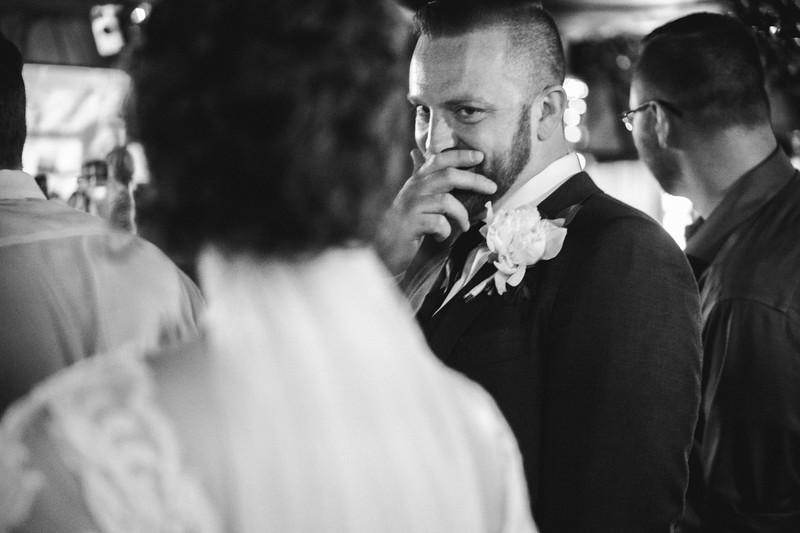 The groom covers his cheeky grin as the bride notices him checking her out.