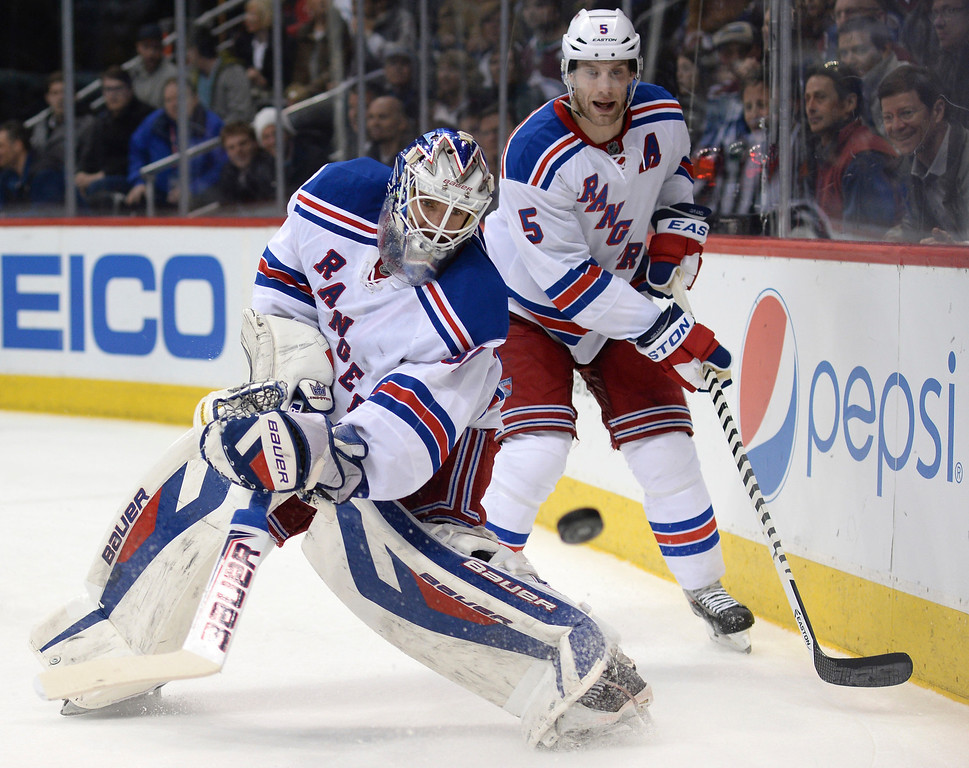 . New York goaltender Henrik Lundqvist cleared the puck late in the third period.  (Photo by Karl Gehring/The Denver Post)
