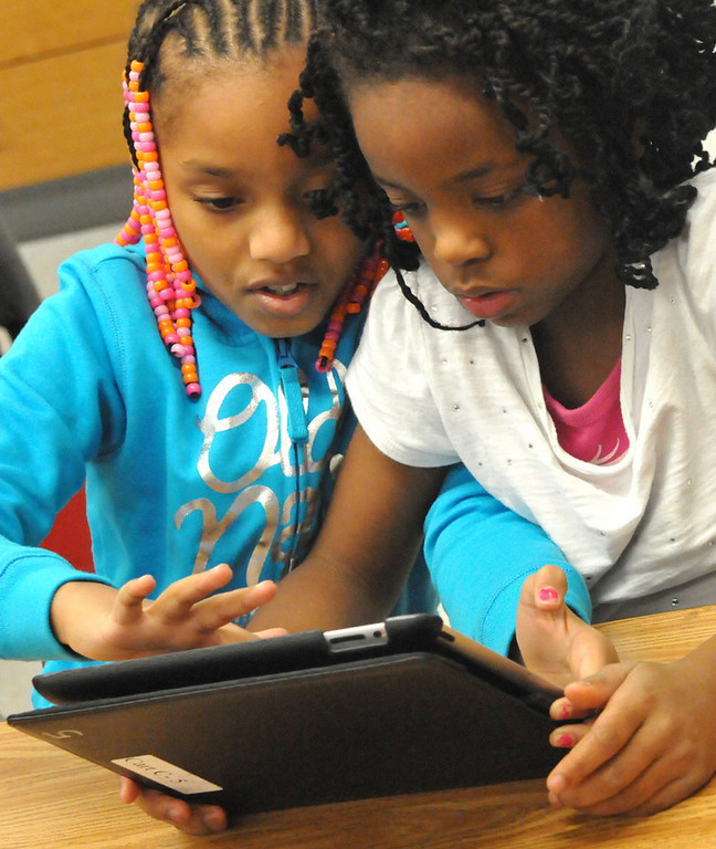 . Third graders Kloi Moore,left and Jhonasia Cross pool their knowledge on a math problem.           (Pioneer Press: John Doman)
