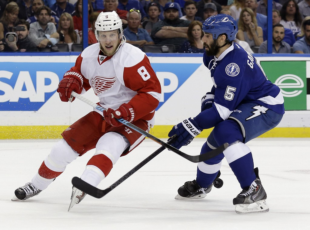 . Tampa Bay Lightning defenseman Jason Garrison (5) knocks the puck away from Detroit Red Wings left wing Justin Abdelkader (8) during the first period of Game 7 of a first-round NHL Stanley Cup hockey playoff series Wednesday, April 29, 2015, in Tampa, Fla. (AP Photo/Chris O\'Meara)