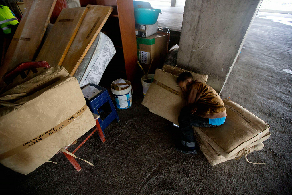 . A boy sleeps on his family\'s belongings as he waits for a truck outside the worldís tallest slum, the Tower of David, a half-built skyscraper that was abandoned in the 1990s and was transformed by squatters into a vertical ghetto, in Caracas, Venezuela, Tuesday, July 22, 2014. Officials and armed soldiers began moving out the first of thousands of squatters who have lived for nearly a decade in a soaring, half-built skyscraper in the heart of Caracas. (AP Photo/Fernando Llano)