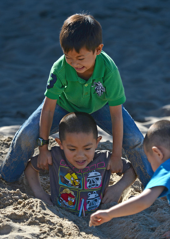 . Taylor Nguyen gives his buddy Dylan Vo a lift out of the sand after he buried himself up to his head. The day after Christmas seemed more like the Fourth of July as people flocked to the beach Thursday, December 26, 2013, in Hermosa Beach, CA.  Photo by Steve McCrank/DailyBreeze