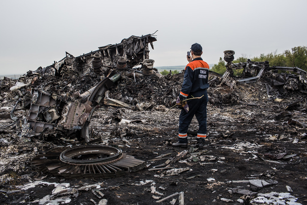 . An emergency services worker photographs debris from an Air Malaysia plane crash on July 18, 2014 in Grabovka, Ukraine. Air Malaysia flight MH17 travelling from Amsterdam to Kuala Lumpur has crashed on the Ukraine/Russia border near the town of Shaktersk. (Photo by Brendan Hoffman/Getty Images)
