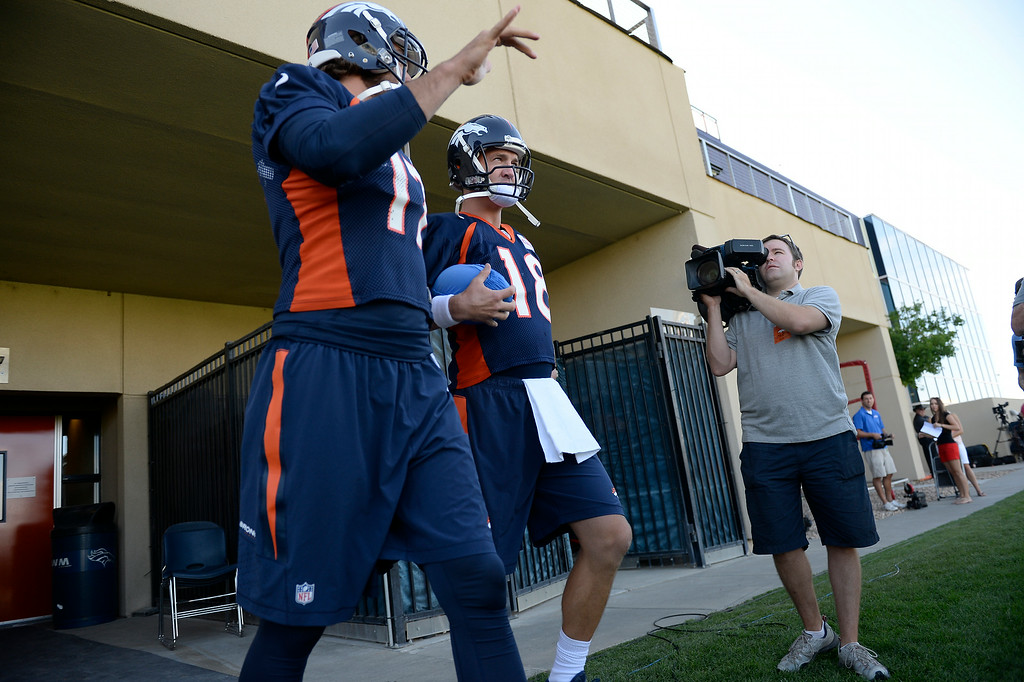 . Denver Broncos quarterback Brock Osweiler (17) and Denver Broncos quarterback Peyton Manning (18) head to the field for the start of the Denver Broncos 2014 training camp July 24, 2014 at Dove Valley. (Photo by John Leyba/The Denver Post)