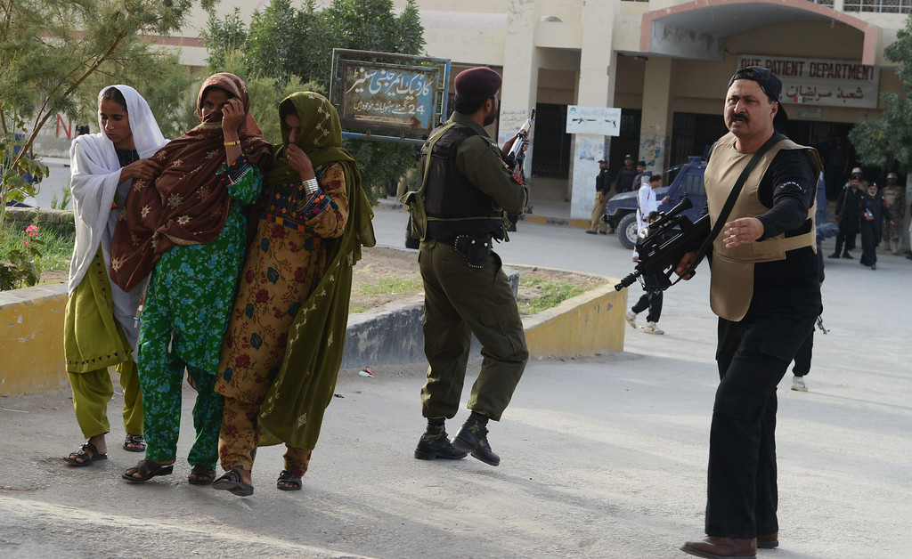 . Pakistani women help a patient (2L) get away from a hospital during a paramilitary operation against militants at a hospital  in Quetta, the capital of Baluchistan province, on June 15, 2013.   AFP PHOTO/ Banaras  KHAN/AFP/Getty Images